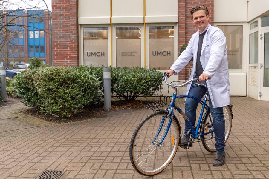 UMCH student on free UMCH / UMFST bike in front of UMCH building