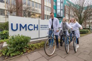 UMCH students in front of UMCH sign on on free UMCH / UMFST bikes